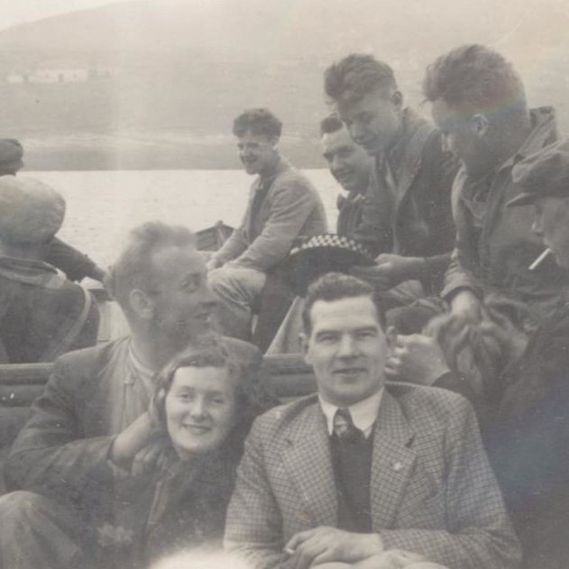 Flour workers sitting in a boat travelling to Isle Martin.  The people look squashed in but cheerful.