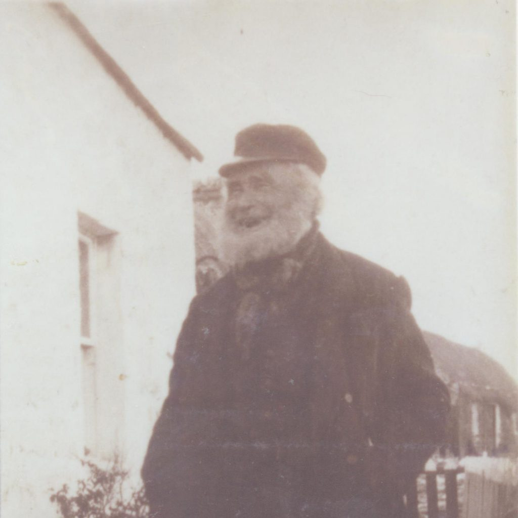 Photograph of William Mathieson outside a white-rendered house on Tanera.  He has his hands in his pockets and is laughing.