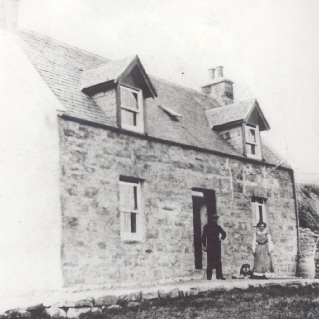 Two figures standing outside a stone cottage with two gable windows.