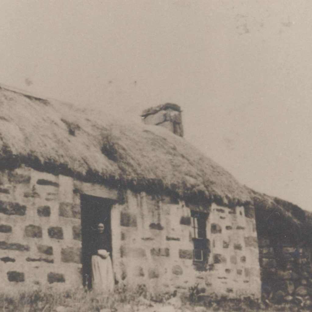 Mrs Macrae standing in the doorway of a single-storey thatched cottage on Isle Martin.